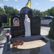 Фото памятника на кладбище. Установленный памятник с барельефом.