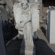 На фото ангел из мрамора с цветами на производстве. Фигура мраморного ангела в галерее скульптуры. Продажа ангелов из мрамора для кладбища.