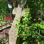 Восстановление памятников. Крест из камня на могиле, подлежащий восстановлению.