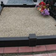 Оформление могилы после установки памятника; фото гранитного цоколя, засыпанного светло бежевой крошкой.